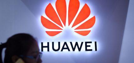 Una Donna Utilizza Il Proprio Smartphone Davanti Ad Un Display LED Di Huawei